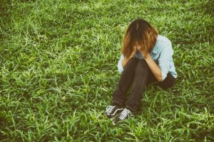 young-woman-sitting-on-the-grass-crying_1150-366